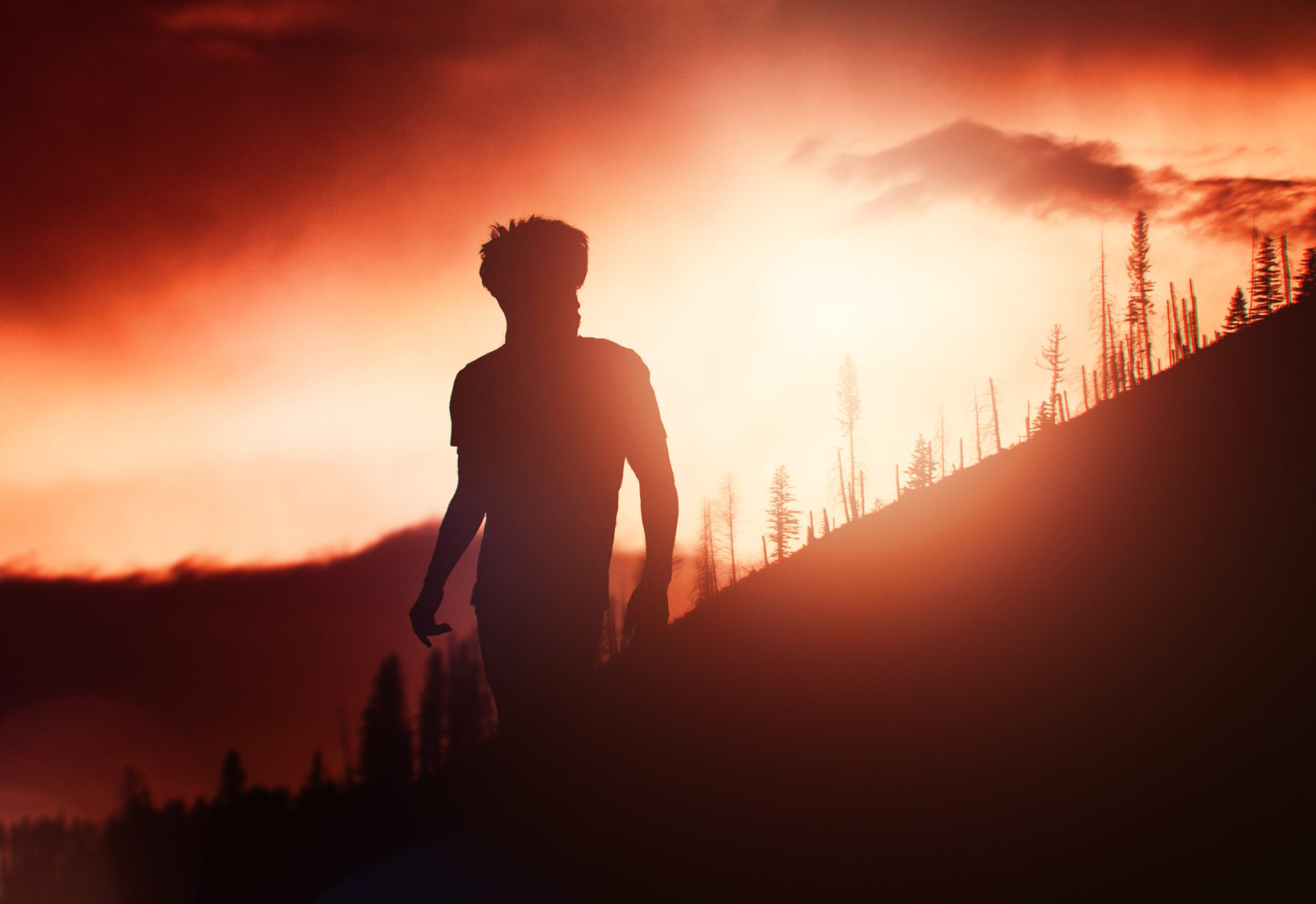a male-presenting person outside on a steep hill silhouetted by a brilliant sun rise.